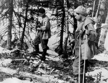 Free search. Suvorov and Askinadzi on the site of the storage. A log, spruce branches and chopped twigs are visible.