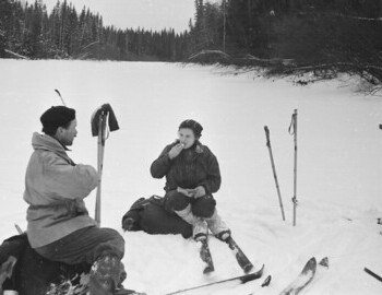 Jan 28 - Halt on Lozva. Zolotaryov and Kolmogorova. A quilted jacket is attached to Zolotaryov's backpack. Visible are spare skis tied with ropes.